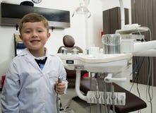 Freundlicher Jungenzahnarzt mit zahnmedizinischer Ausrüstung Lizenzfreies Stockfoto
