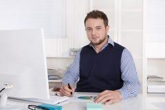Freundlicher junger Geschäftsmann im Porträt, das am Schreibtisch sitzt stockbilder