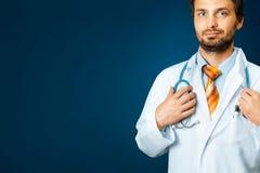 Freundlicher männlicher Doktor In White Coat hält Hand auf Stethoskop Leute-Sorgfalt-Medizin-Versicherungs-Konzept lizenzfreie stockfotos