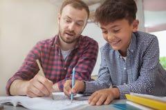Freundlicher männlicher Lehrer, der seinem kleinen Studenten hilft lizenzfreie stockfotos