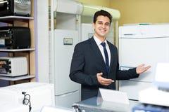 Freundlicher männlicher Verkäufer am Haushaltsgerätabschnitt lizenzfreie stockbilder