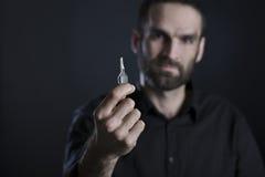 Freundlicher Mann, der einen Schlüssel hält und zeigt Stockfoto