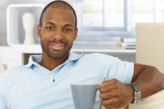 Freundlicher Mann zu Hause, der Tee trinkt stockfotos