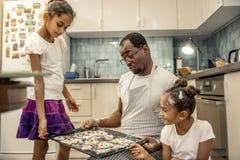 Freundlicher netter Vater und seine Mädchen, die ihre Plätzchen betrachten stockbilder