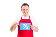 Freundlicher Supermarktangestellter, der Rabattzeichen hält Lizenzfreie Stockfotos