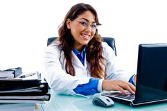 Freundlicher weiblicher Doktor, der an Laptop arbeitet Stockfotografie
