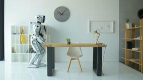 Freundlicher wellenartig bewegender Roboter beim Arbeiten im Büro stock video footage