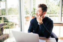 Freundliches Exekutivsitzen vor Laptop in seinem Büro Großes Fenster am Hintergrund Weg schauen, träumend Lizenzfreies Stockfoto