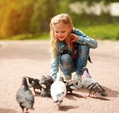 Freundliches frohes M?dchenkind zieht Tauben im Stadtsommerpark ein lizenzfreie stockfotografie
