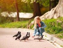 Freundliches frohes M?dchenkind zieht Tauben im Stadtsommerpark ein stockfotografie