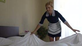 Freundliches Hotelmädchen, das sorgfältig sie Aufgaben, Job, Zeitlupe Bett-machend tut stock video footage