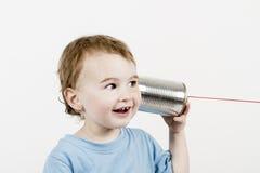 Freundliches Kind, das auf Blechdosetelefon hört stockfoto