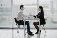 Freundliches lächelndes Geschäftsmann- und Geschäftsfrauhändeschütteln über dem Schreibtisch nach angenehmem Gespräch und effekti stockfotografie