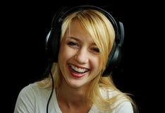 Freundliches lachendes blondes Mädchen in den Kopfhörern Lizenzfreie Stockfotos