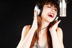 Freundliches Mädchen, das zum Mikrofon singt stockfoto
