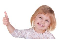 Freundliches Mädchen im weißen Holdingdaumen oben Lizenzfreies Stockfoto