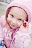 Freundliches Mädchen mit einer Erdbeere Stockfotografie