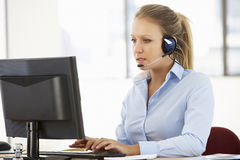 Freundliches Service-Vertreter Talking To Customer im Call-Center Stockfotografie