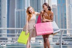 Freundliches shopaholics Zwei schöne Freundinnen im Kleidergriff Stockfoto