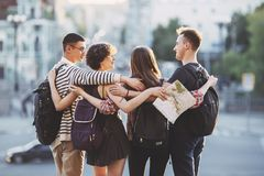 Freundreisende mit dem Rucksackumarmen lizenzfreie stockbilder