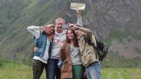 Freundreisende mit Rucksäcken tun selfie am Telefon in den Bergen Eine Gruppe Touristen machen Fotos am Telefon stock video