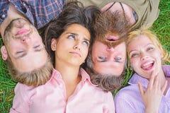 Freundschaft durch ganzes Leben Draufsicht des Firmenfreundlagegrases Blonde oder grobe Hippie-Freunde selben bewegen wellenartig lizenzfreie stockbilder