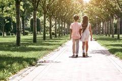 Freundschaft Kleiner Junge und Mädchen, die auf die Straße im Park geht stockfotos