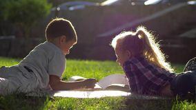 Freundschaft, kleiner Junge und Mädchen, die draußen auf Gras und Ansichtbildern in einem Buch während des Schulbruches im Sonnen stock video footage