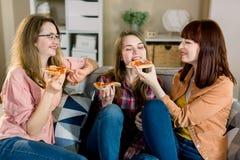 Freundschaft, Leute, Pyjamapartei und Konzept der ungesunden Fertigkost - glückliche junge drei Frauen oder Mädchen, die Pizza, P stockbild