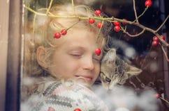 Freundschaft zwischen Mädchen und Katze hinter Fenster Lizenzfreie Stockfotos