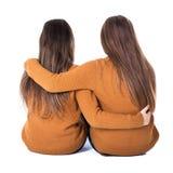 Freundschaftskonzept - hintere Ansicht des Sitzens mit zwei Mädchen an lokalisiert Lizenzfreie Stockfotos