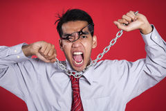 Freustrated businessman with chain shot over red Royalty Free Stock Image
