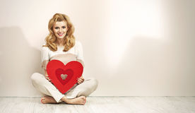 Förförisk blond flicka som rymmer röd hjärta Royaltyfri Fotografi