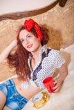 Förförisk röd kvinnlig elevrepresentant på soffan med den retro klockan Arkivfoto