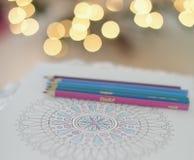 Färga blyertspennor och mandalaboken Arkivbild