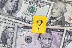 Frågefläck på dollarräkningar Arkivbild