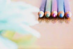 Färgglada eyeliners/blyertspennor med unfocused petals Fotografering för Bildbyråer