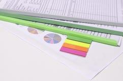 Färgrik anteckningsbok med grafer och dokumentmappar Arkivbild