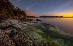 Färgrik kust på natten med stjärnor Arkivfoton
