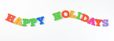 Färgrik text för lyckliga ferier på en vit Royaltyfri Bild