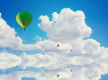 Färgrika ballonger för varm luft som flyger över vatten Royaltyfri Bild