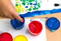 färgrika fingermålarfärger på en tabell Arkivfoton