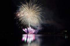 Färgrika fyrverkerier visar med raket som brister ovanför sjön Royaltyfri Bild