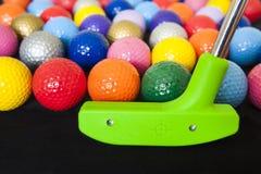 Färgrika golfbollar med den gröna klubban Fotografering för Bildbyråer