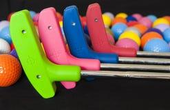 Färgrika golfbollar och puttrar Royaltyfria Bilder