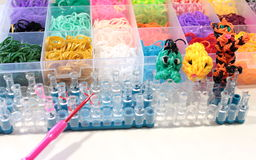 Färgrika gummiband för en regnbågevävstol i en ask Arkivbilder
