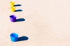 Färgrika hinkar på strandsanden Arkivbild