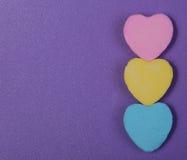Färgrika hjärtor. Godis för tre älskling över purpurfärgad bakgrund Arkivbilder