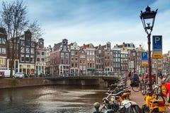Färgrika hus och cyklar på kanalen seglar utmed kusten, Amsterdam Arkivfoton