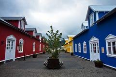 Färgrika röda, blåa och gula hus på Siglufjordur härbärgerar Arkivfoton